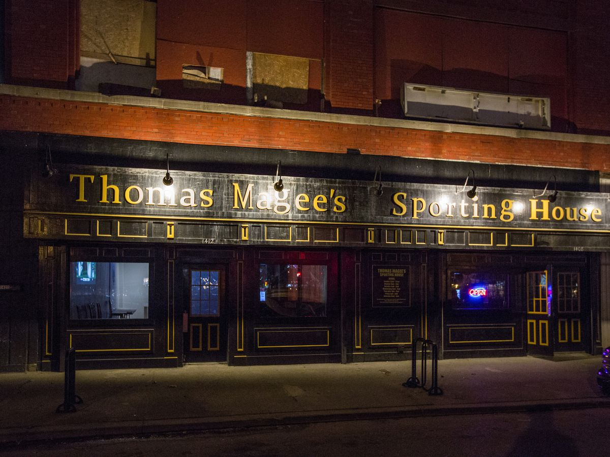 A sign outside a dark, closed building reads Thomas Magee's Sporting House