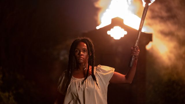 janelle monae holds a torch at night in antebellum