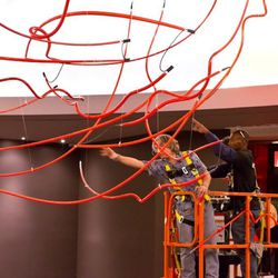 Artist Andrey Berezowsky, left, supervises the installation of a neon light overhead that was inspired by Gordon Ramsay's hand gestures as he cooks.