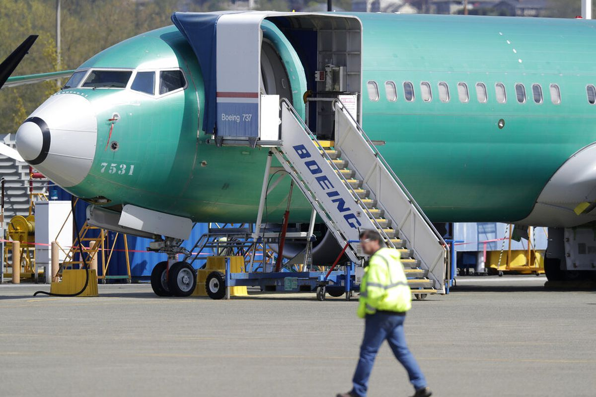 A worker walks past a Boeing 737 MAX 8 airplane being built for Oman Air at Boeing's assembly facility in Renton, Wash.