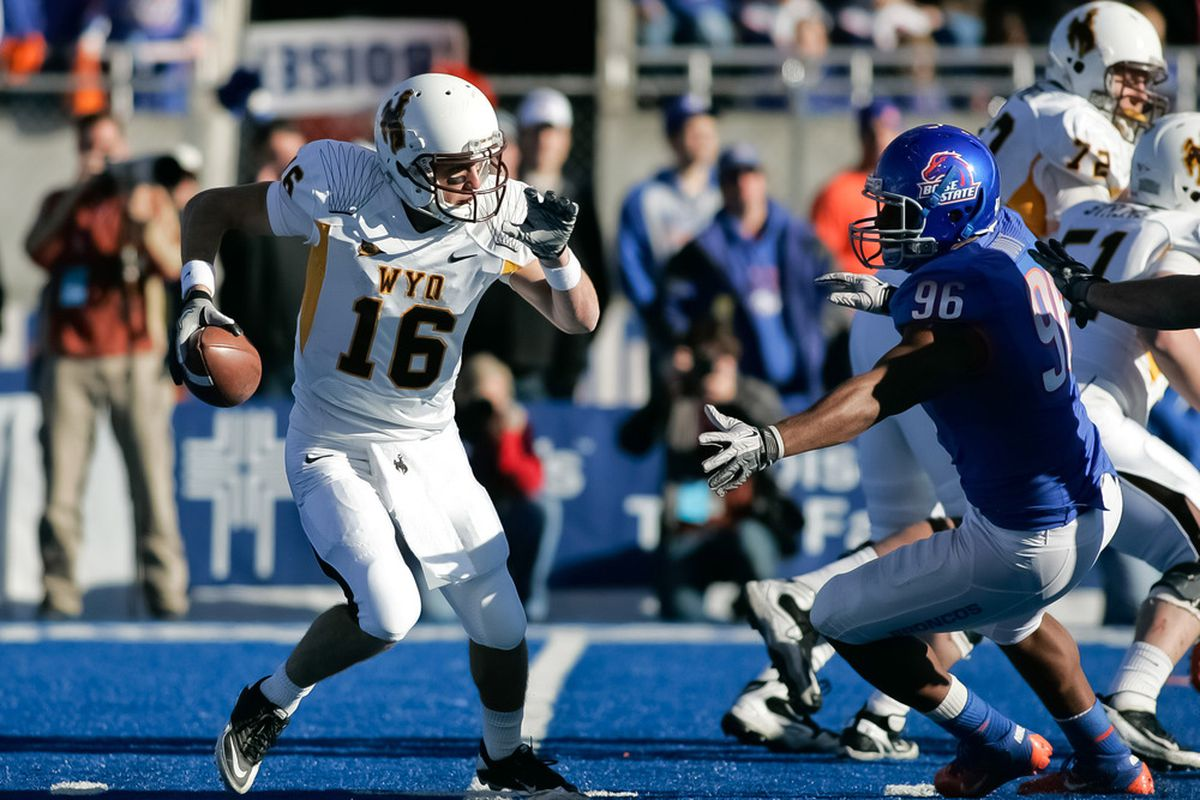 BOISE, ID - NOVEMBER 26: Brett Smith #16 of the Wyoming Cowboys moves to escape Jarrell Root #96 of the Boise State Broncos at Bronco Stadium on November 26, 2011 in Boise, Idaho.  (Photo by Otto Kitsinger III/Getty Images)