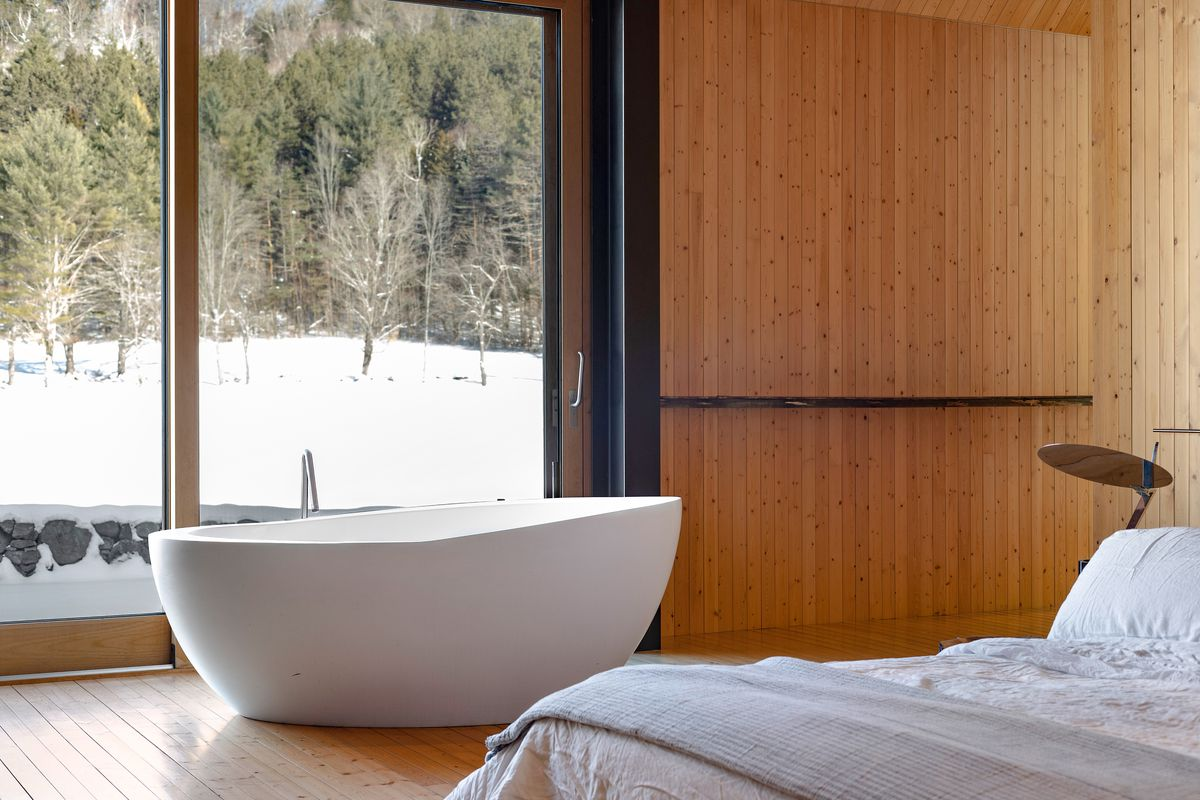 A white tub sits in front of a glass window looking out on the snow.