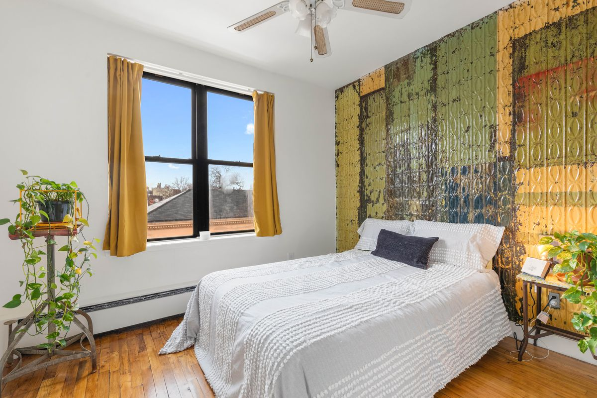 A bedroom with a wall made out of a repurposed tin ceiling, a window, a planter, and a ceiling fan.