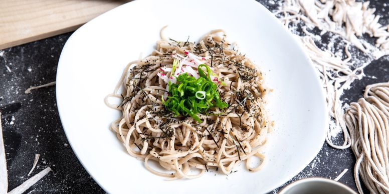 A bright, shallow, wide bowl about half full of soba noodles topped with slivers of radish and scallions, on a countertop spread with raw noodles and flour