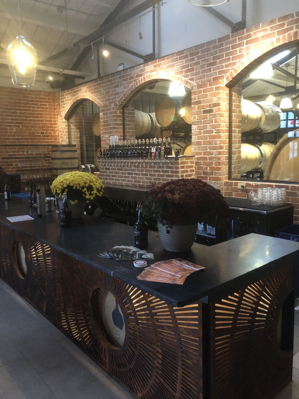 A photo of the bar in the tasting room with a bartop with pots containing flowers on it and several wine taps visible behind it