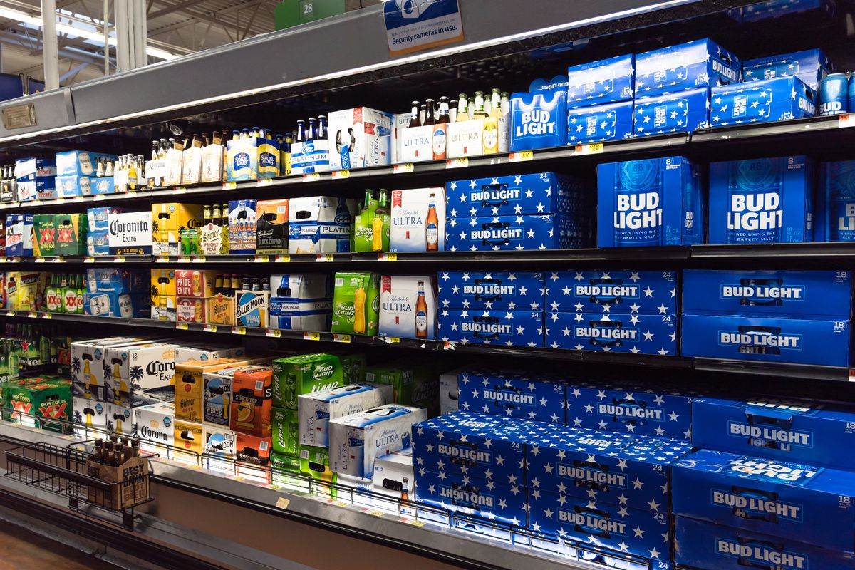 Rows of beer cans and bottles in a supermarket fridge case