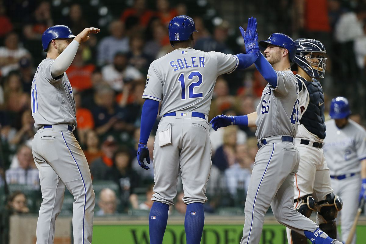 Ryan O'Hearn #66 of the Kansas City Royals receives a high five from Jorge Soler #12 and Hunter Dozier #17 after hitting a grand slam in the third inning against the Houston Astros at Minute Maid Park on May 07, 2019 in Houston, Texas.