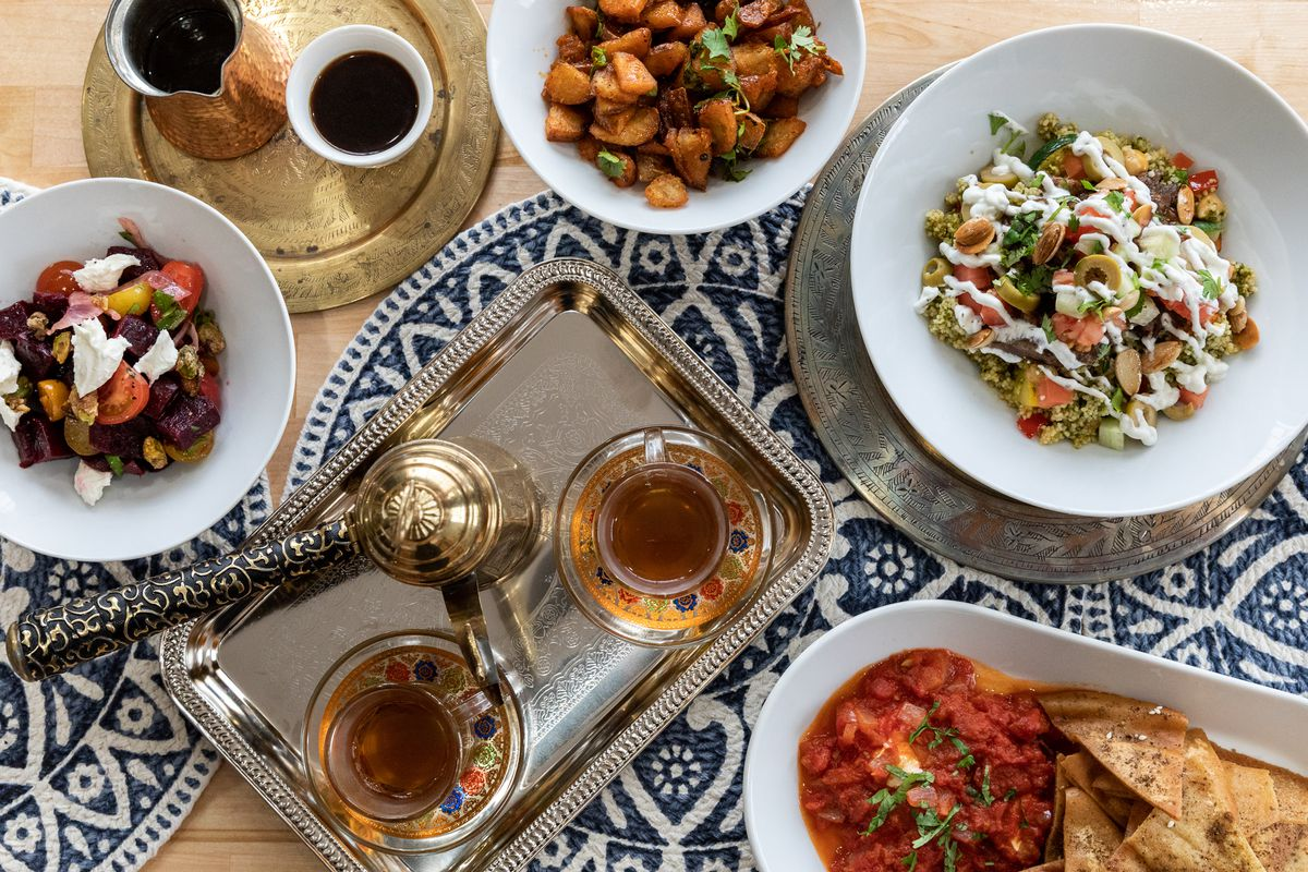 A Moroccan tea set, a red dip with pita chips, a lamb tagine, harissa potatoes, coffee, and more on a wooden table with blue and white-patterned woven center pieces.
