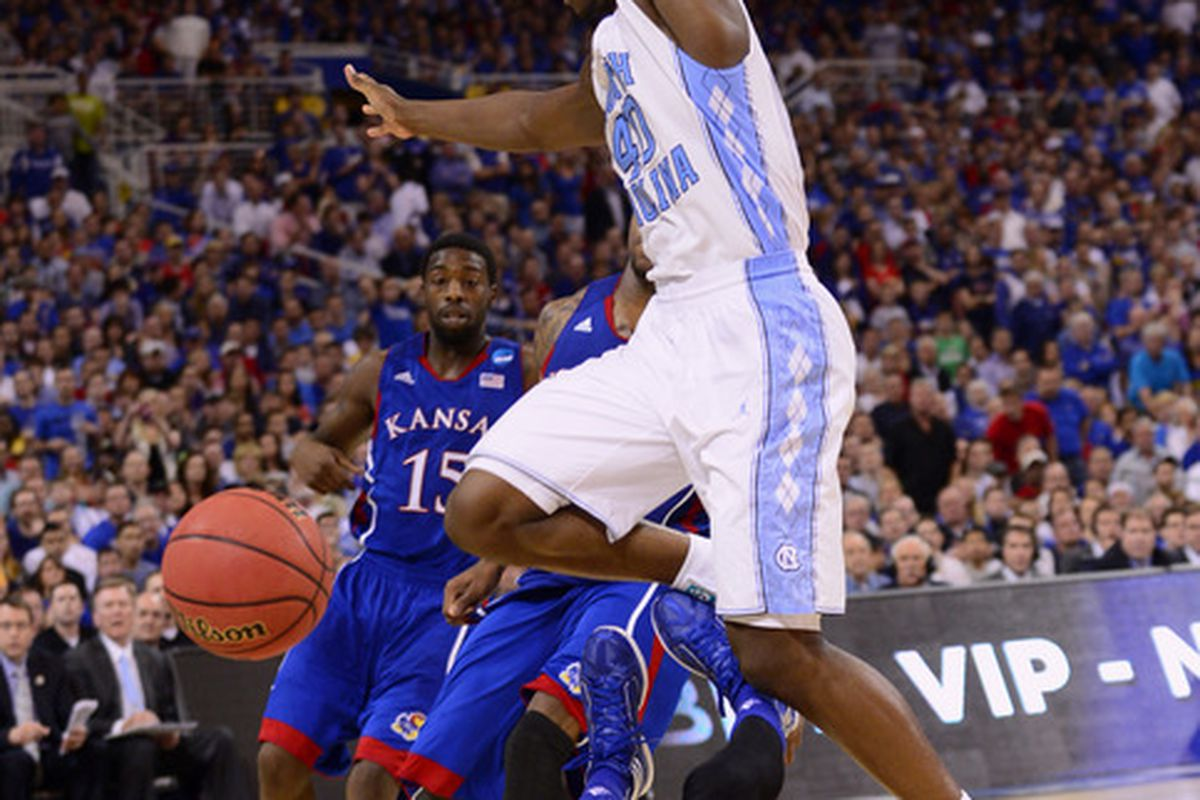 Harrison Barnes jumps over Kansas Jayhawks guard Tyshawn Taylor (10) after losing control of the ball during the second half of the finals of the midwest region of the 2012 NCAA men's basketball tournament at the Edward Jones Dome.