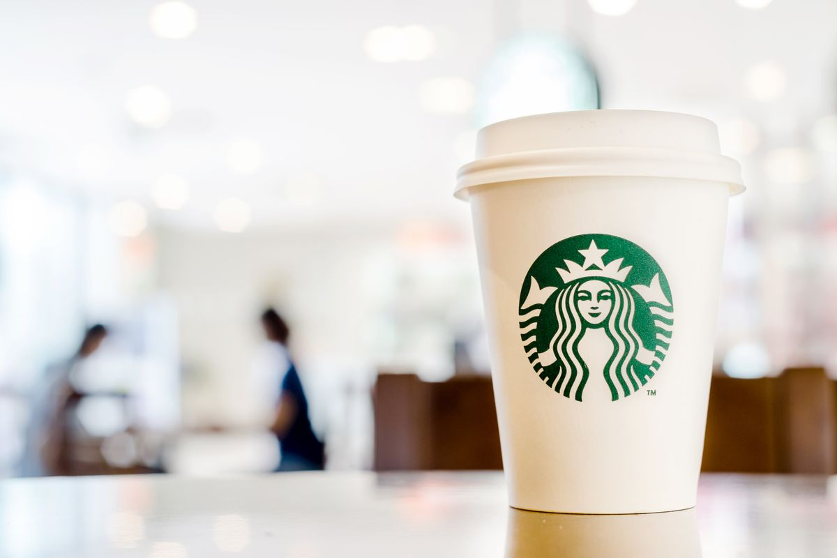 A paper Starbucks cup sitting on a wooden counter with customers blurred in the background