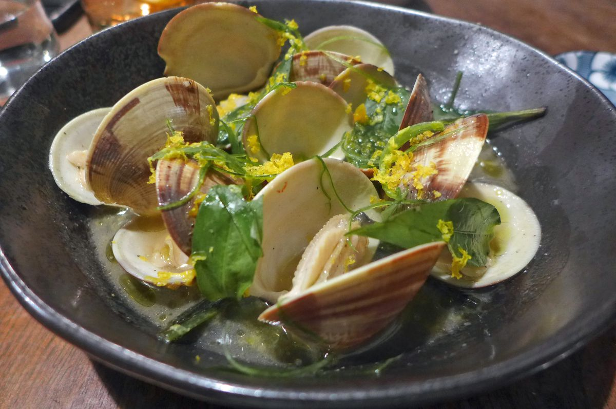 Clams in their shells festooned with green lemongrass.