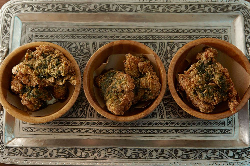 Overhead view of three bowls of fried chicken, garnished with herbs and served on a Turkish-style silver platter
