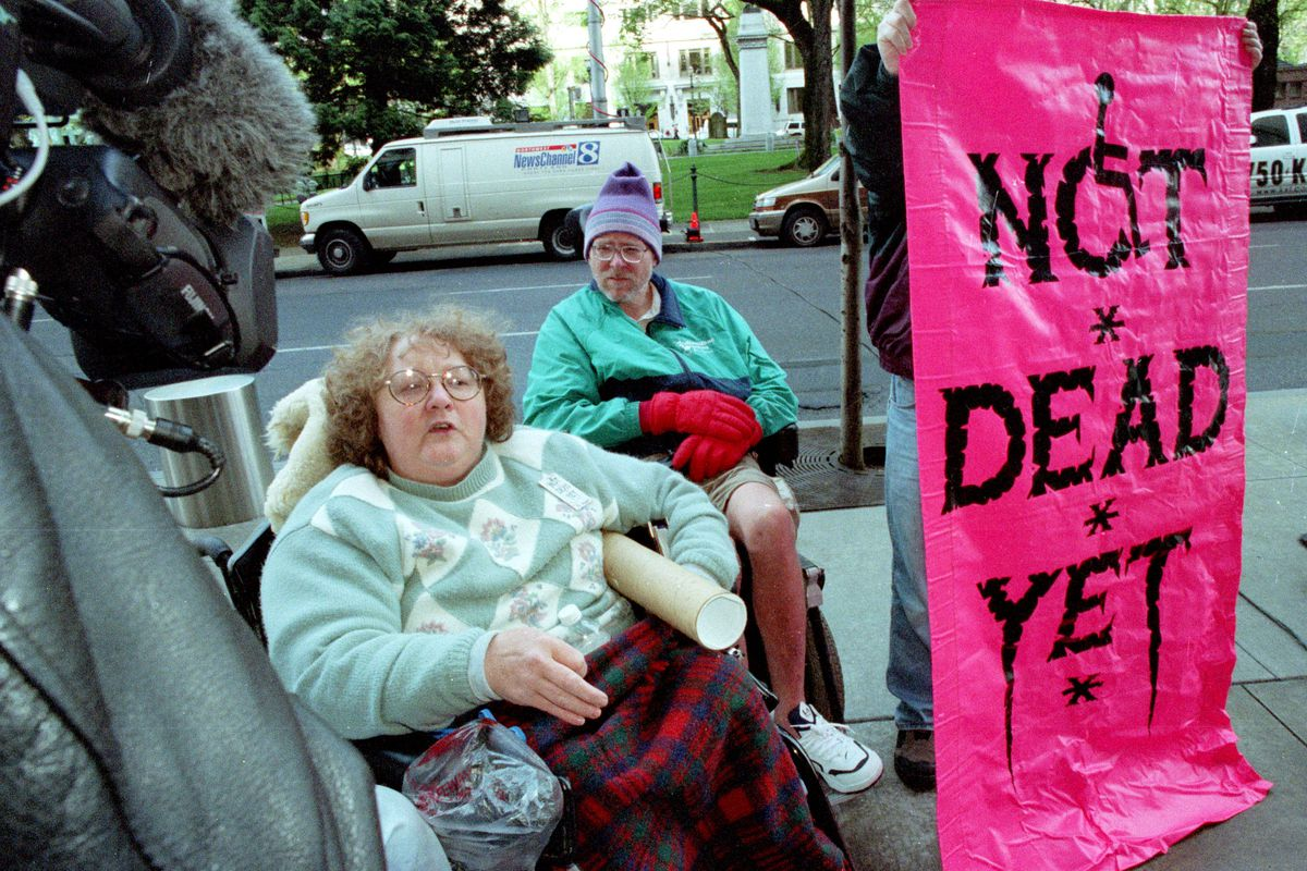 Ellie Jenny (L) and Brock Miller from the disability rights organization Not Dead Yet demonstrate against a federal judges ruling upholding physician-assisted suicide April 17, 2002 in Portland, OR.