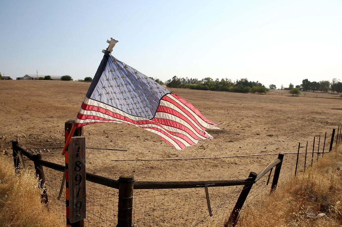 An American flag is posted on a fence in front of a dry unplanted field on August 8, 2014 in Lodi, California. (Photo by Justin Sullivan/Getty Images)