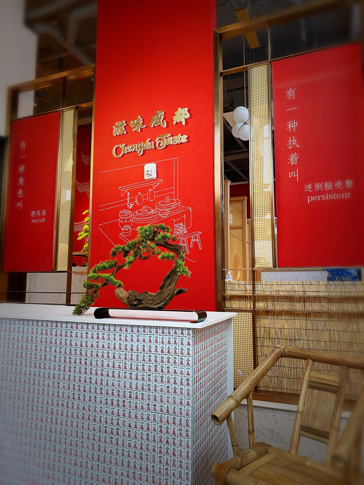The front of Chengdu Taste, with the restaurant's sign embossed in gold against a red background, with Chinese lettering below it