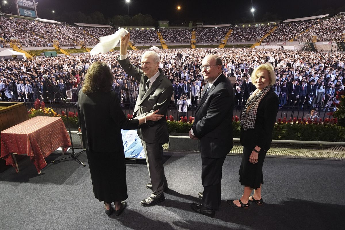 President Russell M. Nelson of The Church of Jesus Christ of Latter-day Saints waves a hankerchief after a devotional at Estadio Cementos Progreso stadium in Guatemala City on Saturday, Aug. 24, 2019. Sister Wendy Nelson, Elder Quentin L. Cook, Quorum of the Twelve Apostles, and his wife sister Mary Cook look at the choir.