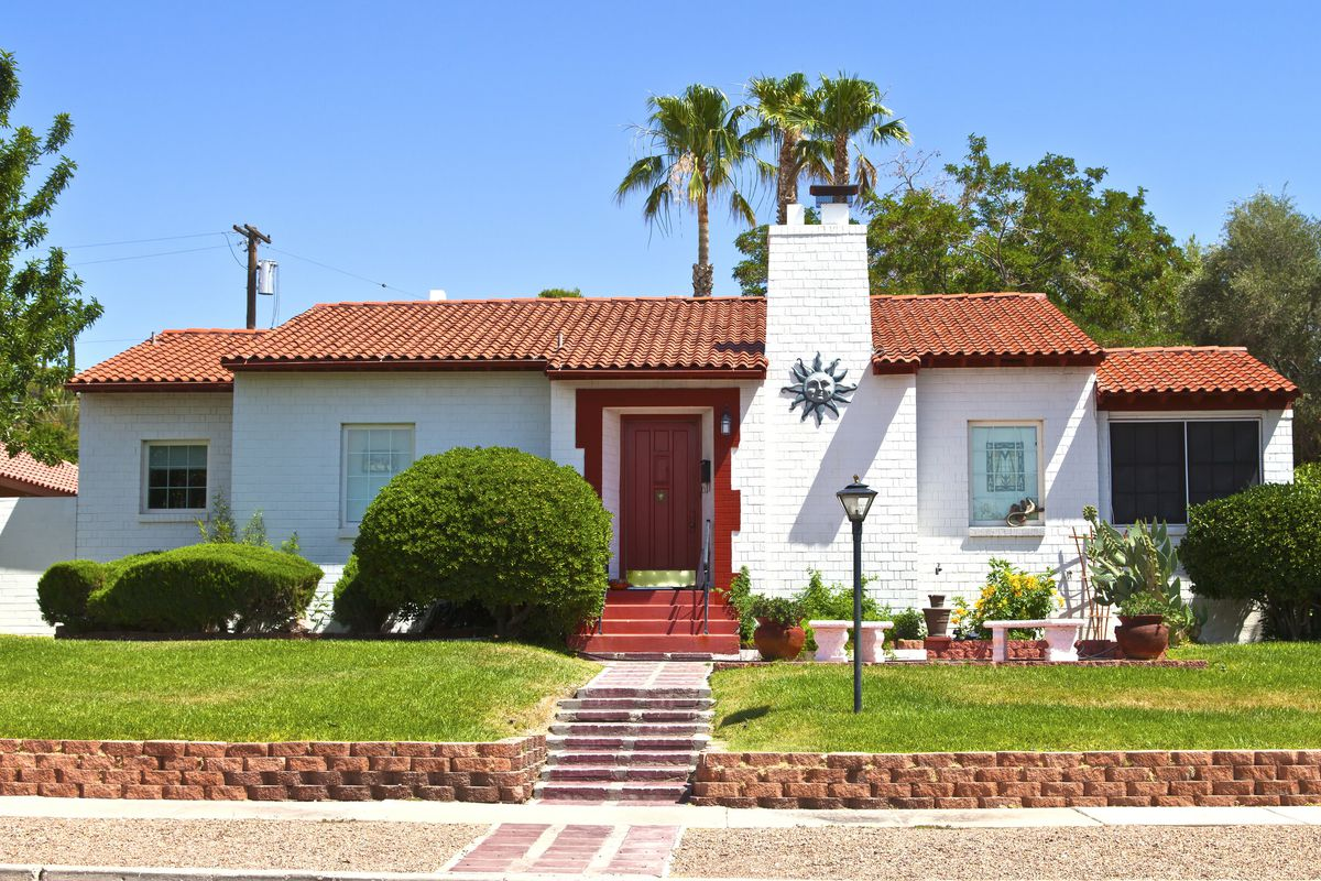 A white home in Nevada with a Spanish roof, red front door, green yard, and planters.