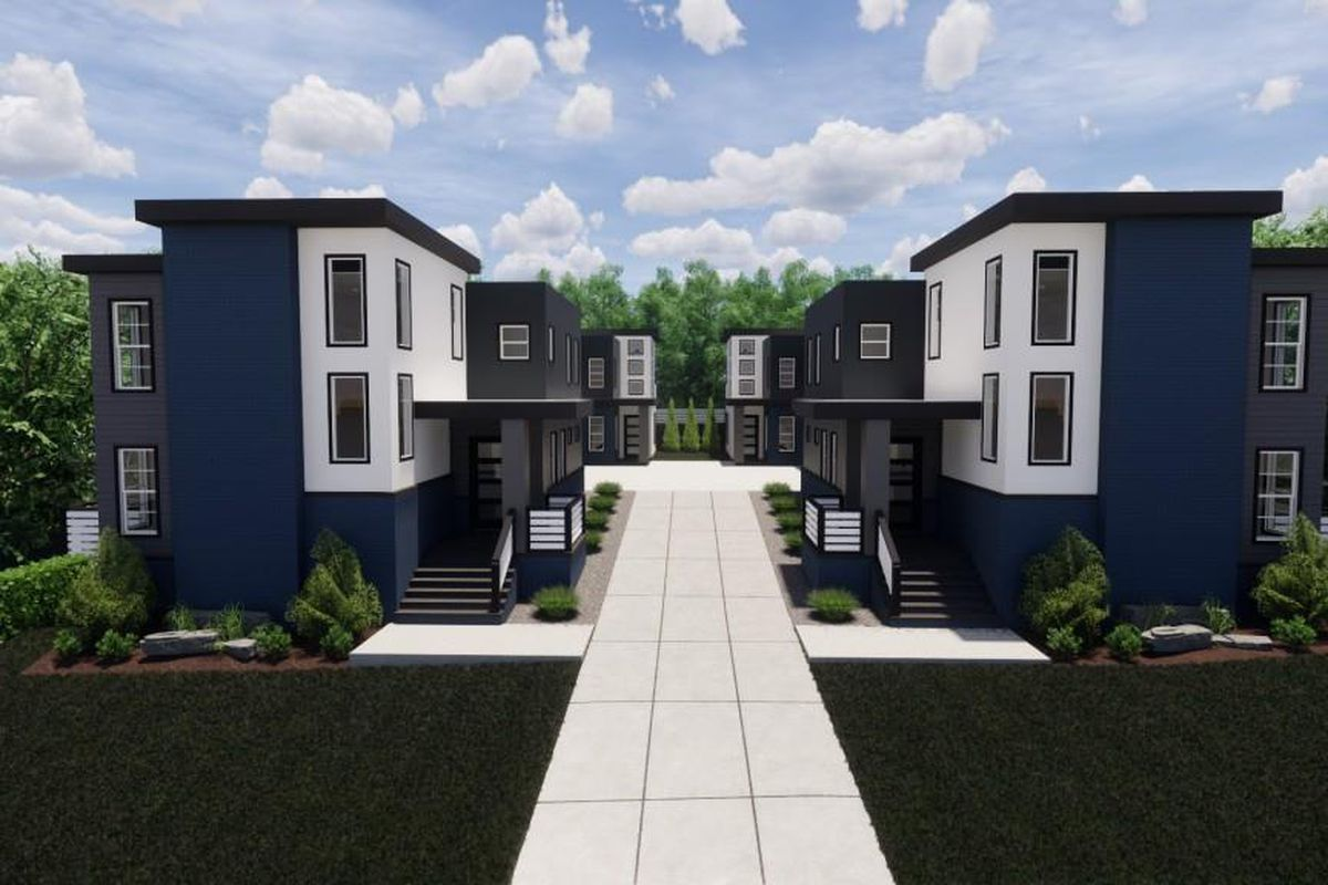 A blue and white townhome complex set off a street with many trees around.