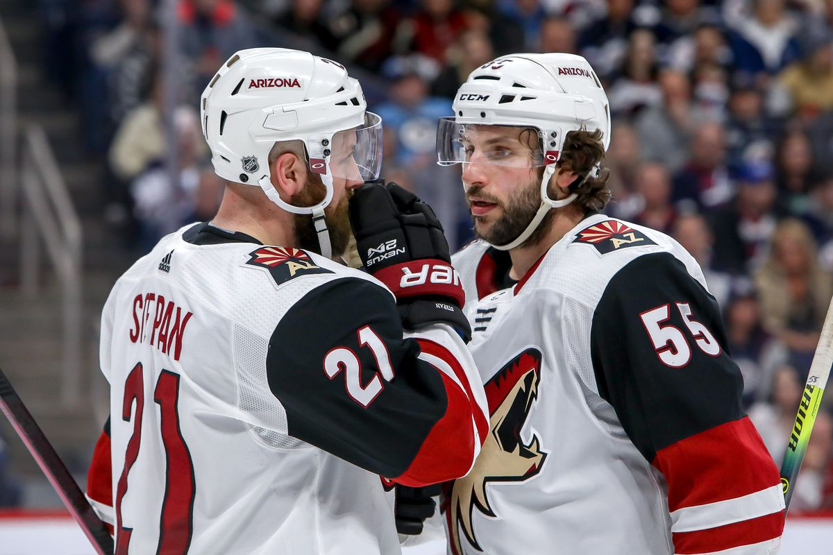 WINNIPEG, MB - MARCH 9: Derek Stepan #21 and Jason Demers #55 of the Arizona Coyotes discuss strategy during a second period stoppage in play against the Winnipeg Jets at the Bell MTS Place on March 9, 2020 in Winnipeg, Manitoba, Canada.