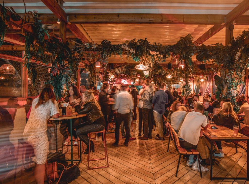 People drinking at Lost in Brixton, a buzzy rooftop spot within Brixton Market