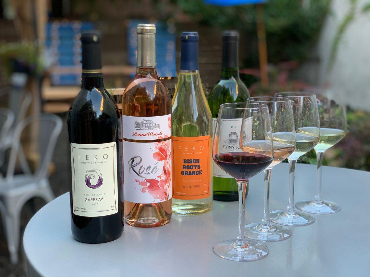 row of wine bottles next to wine glasses