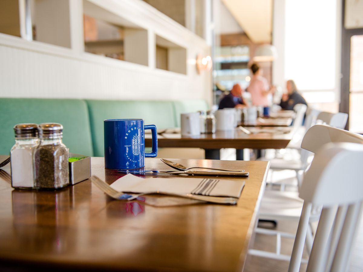 A light-filled restaurant interior with white walls, aquamarine booths, wood tables, and white chairs