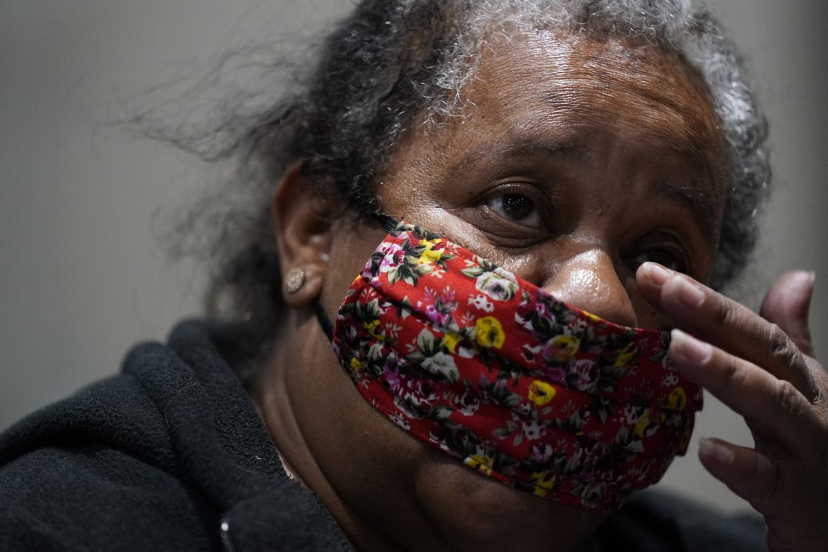 Virginia McShane, 63, wipes her eyes while staying at a homeless shelter inside the San Diego Convention Center Tuesday, Aug. 11, 2020, in San Diego.