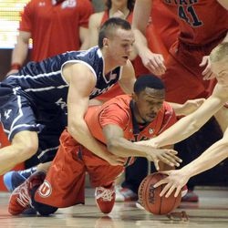 Brigham Young Cougars guard Kyle Collinsworth (5) and Brigham Young Cougars forward Eric Mika (00) fight for a loose ball with Utah Utes guard Ahmad Fields (13) during a game at the Jon M. Huntsman Center on Saturday, December 14, 2013.
