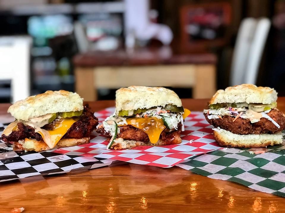 Three fried chicken sandwiches on a table.