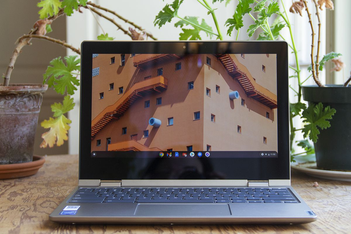 The Lenovo Ideapad Flex 3 Chromebook sits open on a table in front of two houseplants. The screen displays the upper windows of a large building.