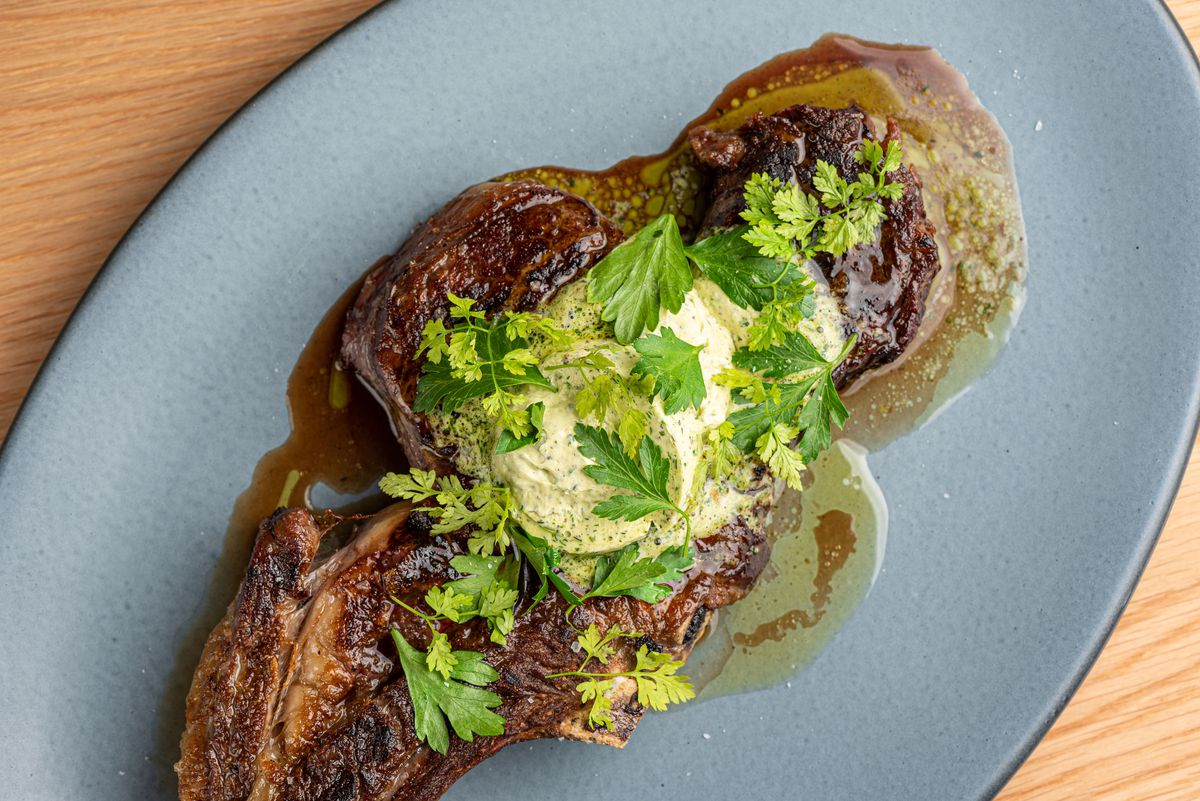 A narrow, thick cut of deeply burnished steak with butter and greens.