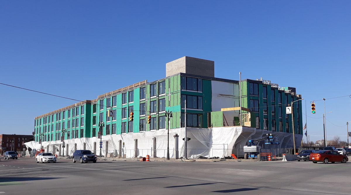 A green building that is under construction with a construction tarp hanging over it's entire lower level.