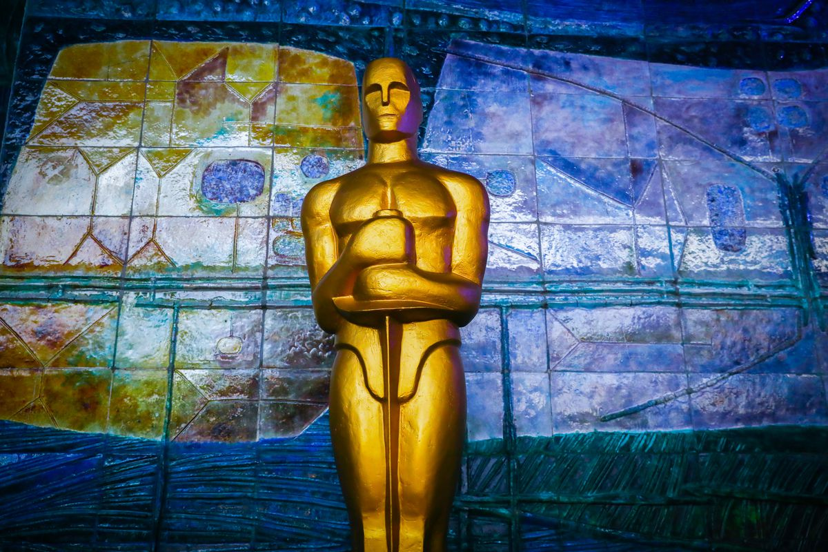 An Oscar statue in front of a colorful background.
