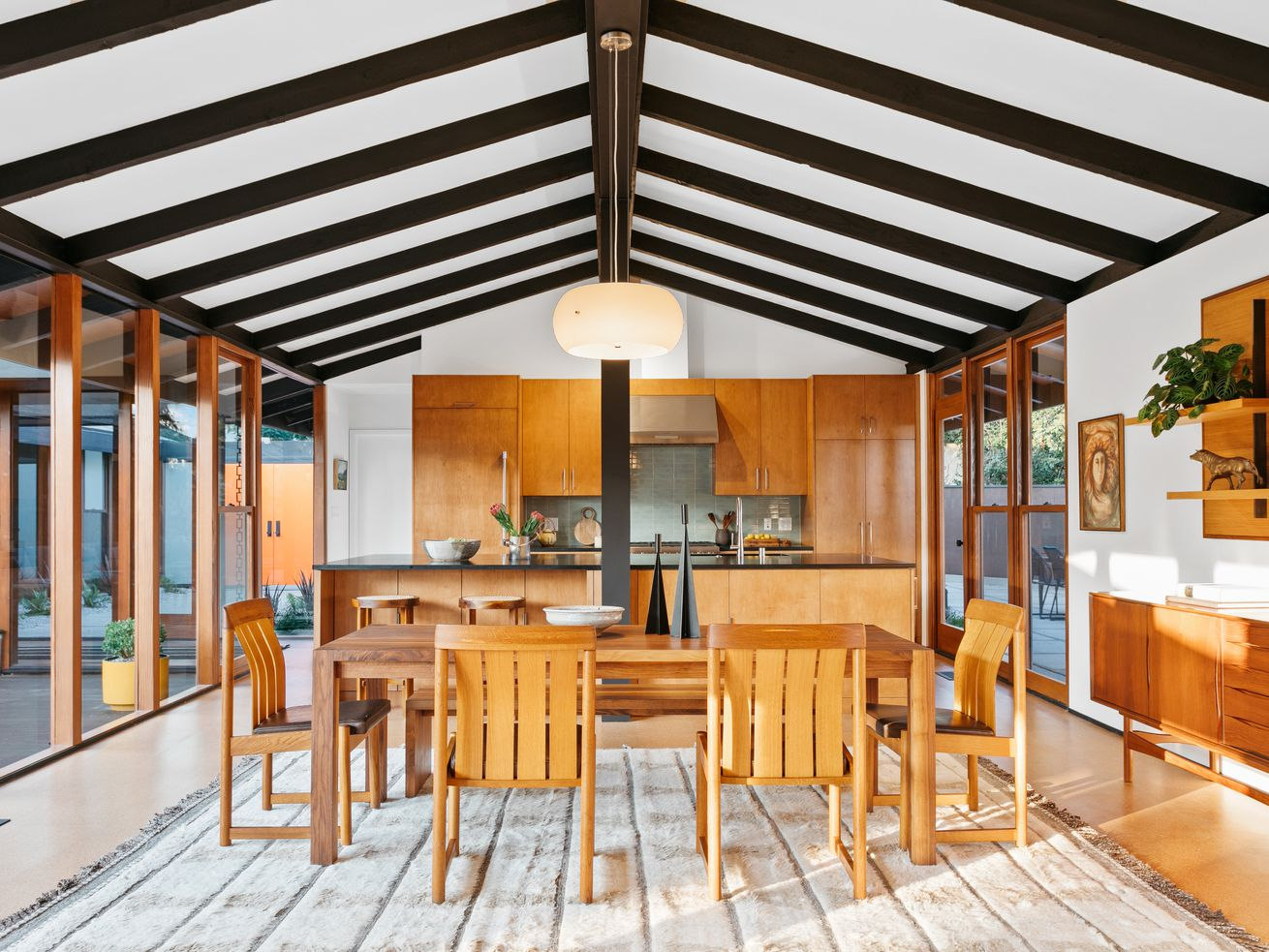 A room with vaulted ceilings and glass walls, furnished with a large wooden table and chairs. Kitchen counter space is visible int the background.