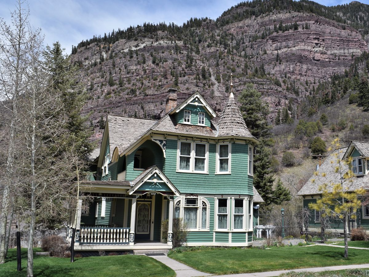 A large green Victorian house with a grey roof. The house is in the foreground. There are mountains in the background.