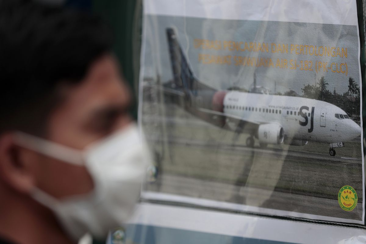 In this in this Jan. 10, 2021, file photo, a man walks past a picture of a Sriwijaya Air passenger jet that crashed off Java island, put up at the command center for the search and rescue mission at Tanjung Priok Port in Jakarta, Indonesia.