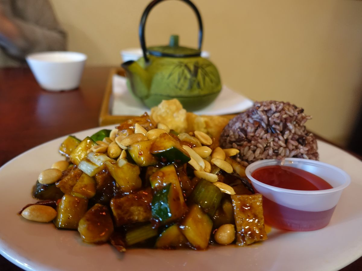 A plate of zucchini, eggplant, tofu, and peanuts, with a side of orange sauce and a dollop of rice.