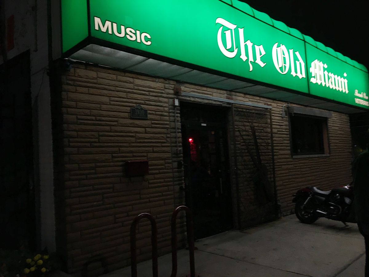 The green awning for Old Miami is lit up at night with a motorcycle parked out front.