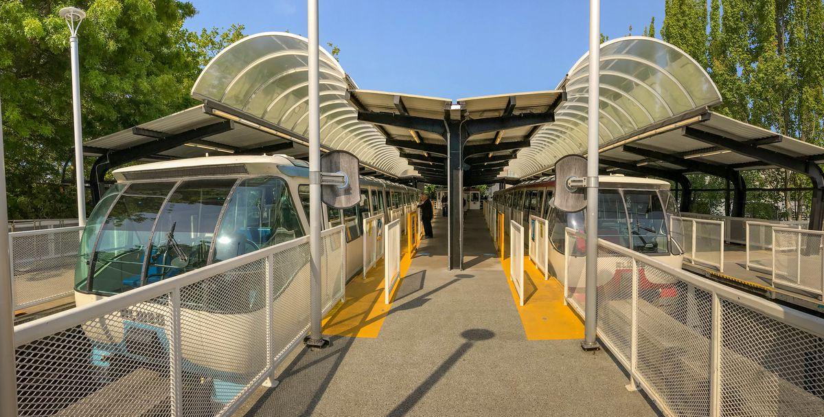 A train platform with a center waiting area and an awning covering a train on either side. The platform and bays are separated by white metal grates. There are trees on either side.