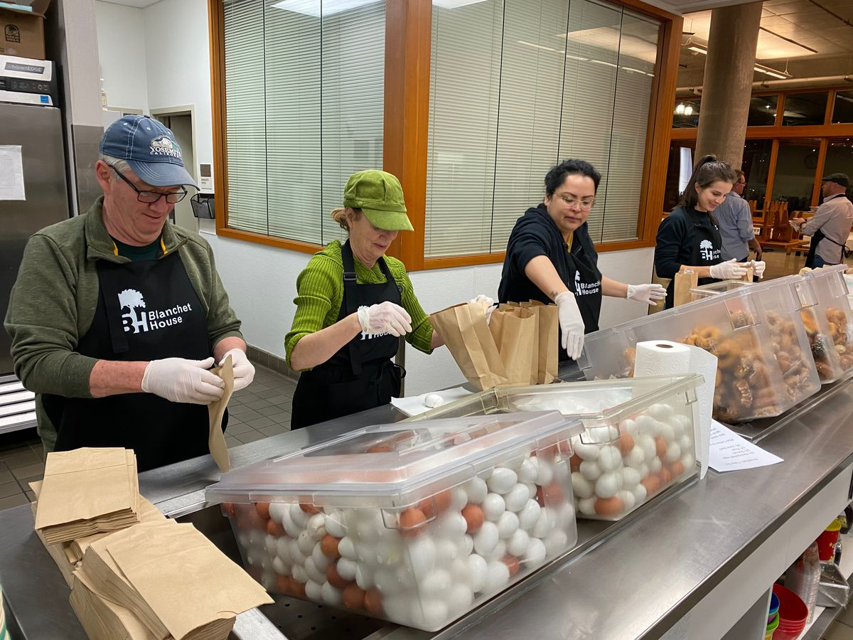 A line of volunteers start packing paper bags filled with hard-boiled eggs and oranges for food insecure diners. They're wearing gloves and aprons, with large tubs of food in front of them.