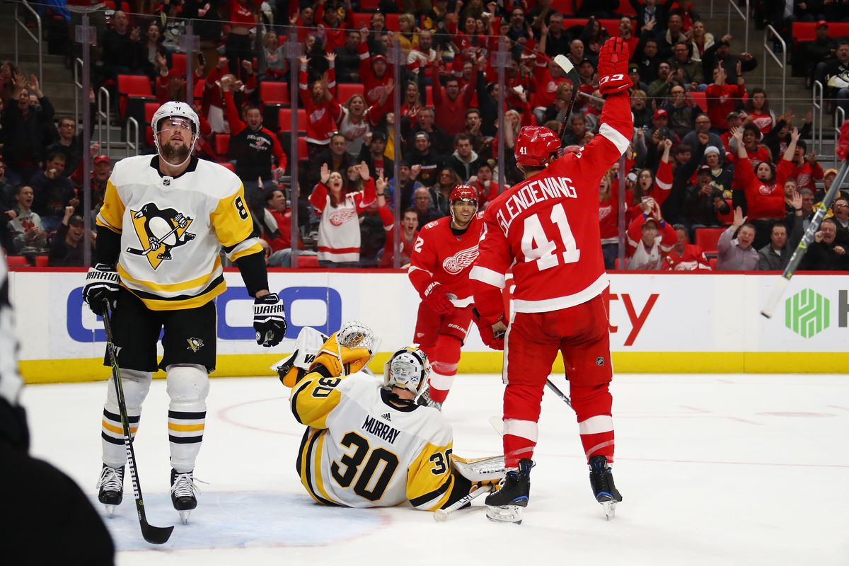 DETROIT, MI - MARCH 27: Luke Glendening #41 of the Detroit Red Wings celebrates a second period goal next to Matt Murray #30 and Brian Dumoulin #8 of the Pittsburgh Penguins at Little Caesars Arena on March 27, 2018 in Detroit, Michigan.