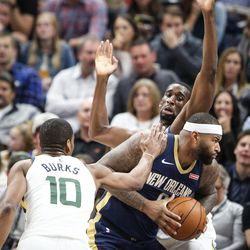 New Orleans Pelicans center DeMarcus Cousins (0) tries to turn and shoot on Utah Jazz center Ekpe Udoh (33) while guard Alec Burks (10) tries to reach in and strip the ball as Utah hosts New Orleans at Vivint Arena in Salt Lake on Friday, Dec. 1, 2017.
