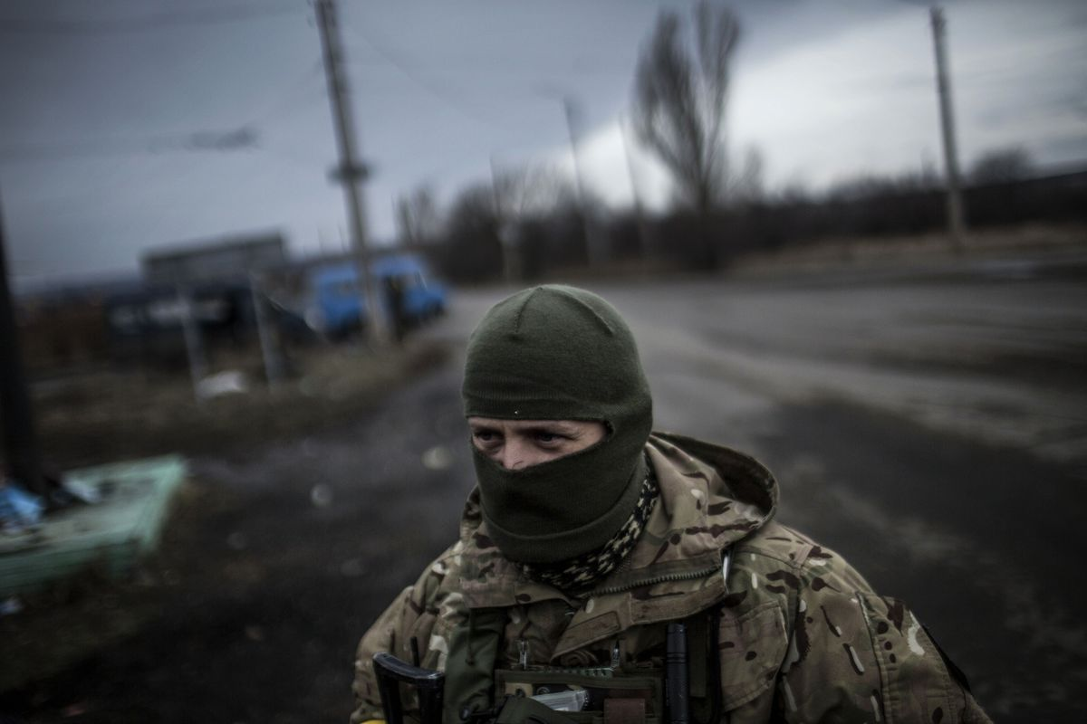 A Ukrainian soldier stands watch near the front lines with pro-Russian separatist rebels.