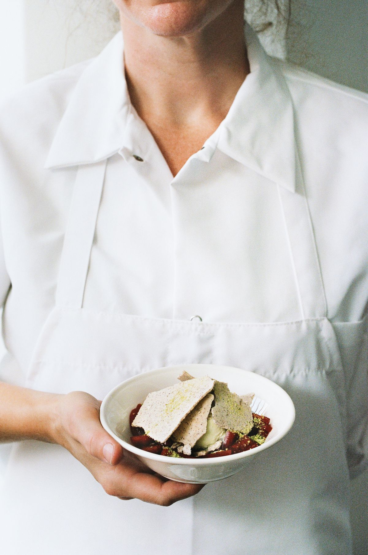 A worker in a white uniform holds a dessert in a bowl.