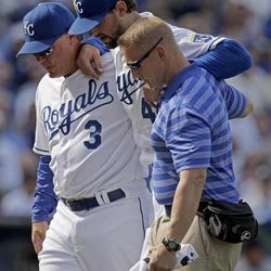 Kansas City Royals starting pitcher Luke Hochevar, center, is helped off the field by manager Ned Yost, left, and trainer Nick Kenney after being hit by a ball  during the fourth inning of a baseball game on Friday, April 13, 2012, in Kansas City, Mo.