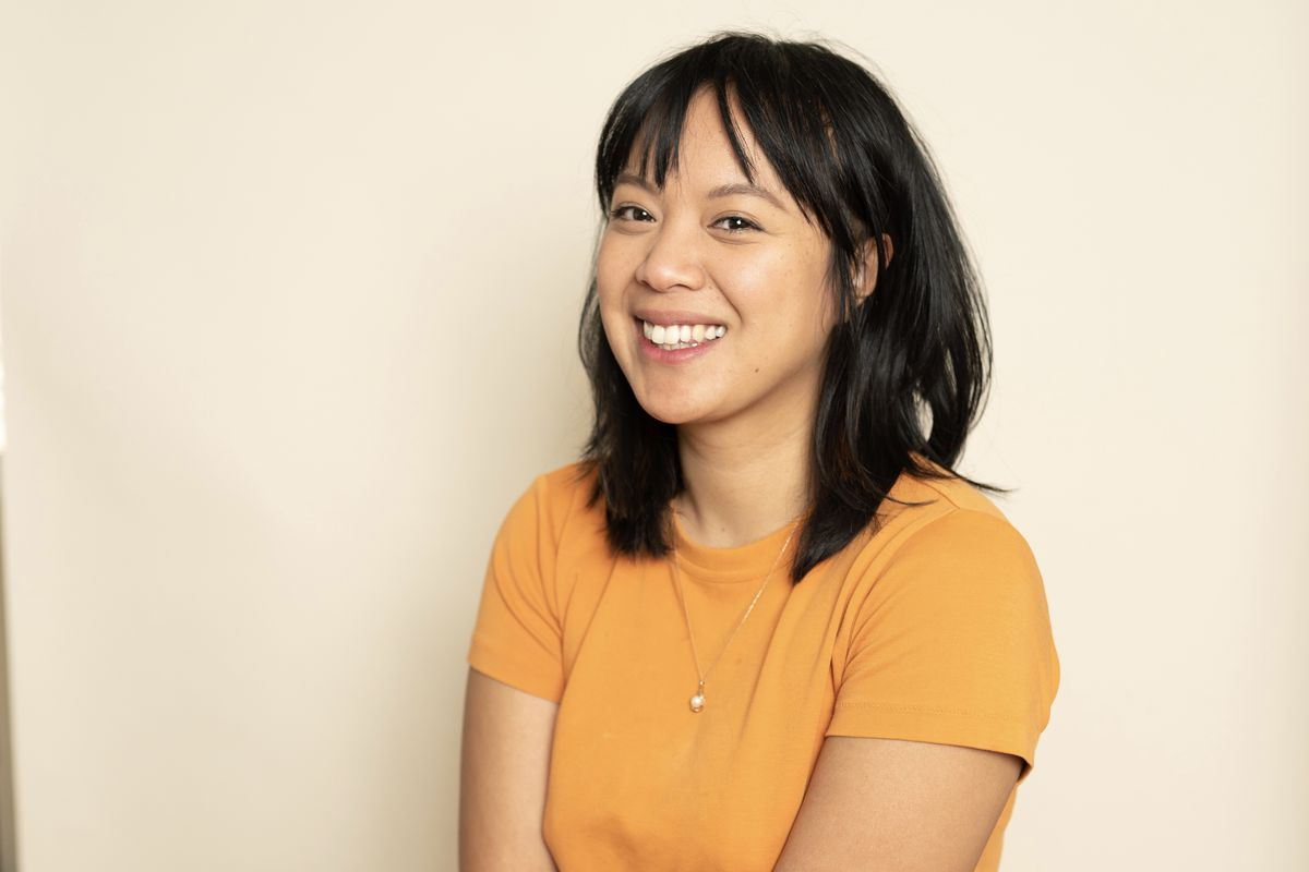 Diane Lam sits in front of a beige wall wearing a yellow-orange shirt. She is a young Cambodian-American woman with black hair and bangs.