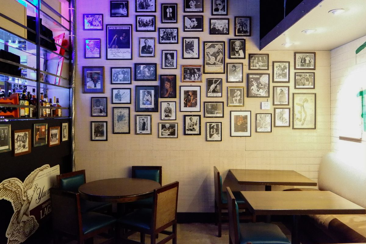 Three restaurant tables with tan tables sitting in front of a collage of photography again't a white brick wall