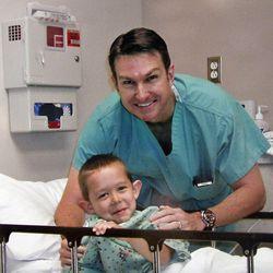 Kamden Gill poses with Dr. Steven Mobley before Kamden undergoes ear-pinning surgery.