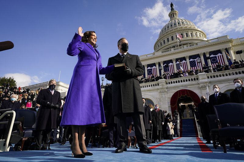 Kamala Harris gives the oath of office with her hand on a Bible held by her husband Doug Emhoff.