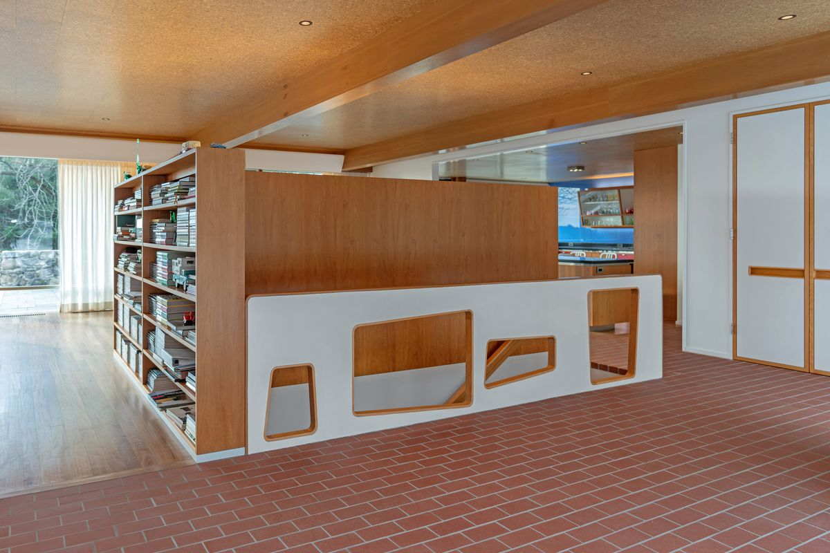 A look at custom built cabinets that sit next to a brick floor.